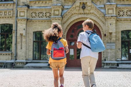 back view of two multicultural schoolkids with backpacks running in schoolyard Stockfoto
