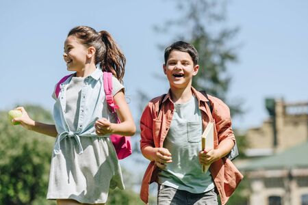 two happy schoolkids with backpacks smiling while running in park