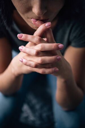 Cropped view of depressed woman with clenched hands at home Stock Photo