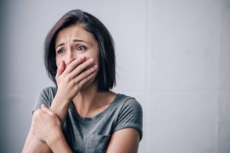 depressed brunette woman covering mouth and crying at home Stock Photo