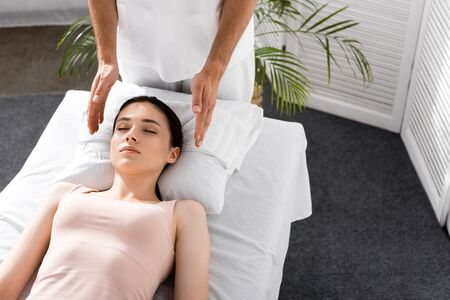 cropped view of healer standing near patient on massage table and cleaning aura