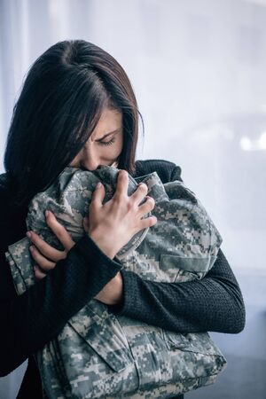 depressed woman crying and holding military clothing at home