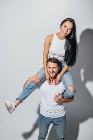 young man holding girlfriend on shoulders while smiling and looking at camera Stockfoto