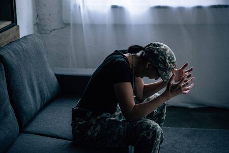 depressed woman in military uniform screaming at home