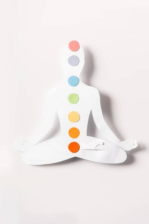 top view of paper figure in form of person with chakras in lotus pose on white Stockfoto