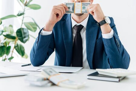 panoramic shot of businessman covering face while smelling dollar banknotes