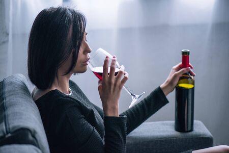 Mujer solitaria deprimida sentada en el sofá y bebiendo vino en casa
