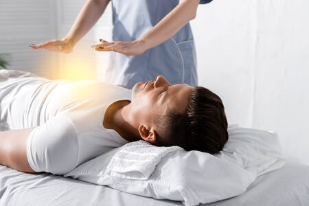 partial view of healer standing near man on massage table and holding hands above his body Stock Photo