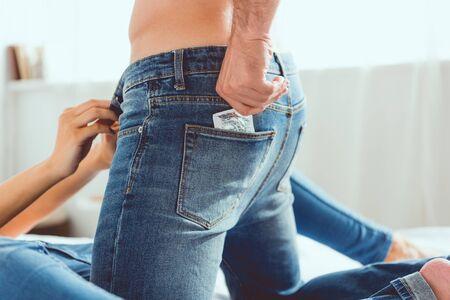 青いジーンズを着た青いジーンズの若い男のトリミングされたビューは、ガールフレンドの近くのポケットからコンドームを取得 写真素材
