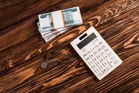 vista dall'alto della calcolatrice bianca vicino ai soldi russi sul tavolo di legno