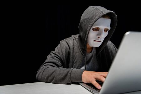 anonymous internet troll in mask typing on laptop keyboard isolated on black Stock Photo