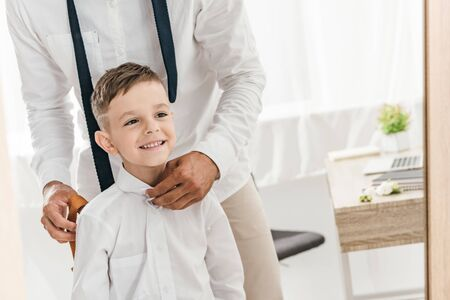 partial view of father and son in white shirts getting dressed near mirror