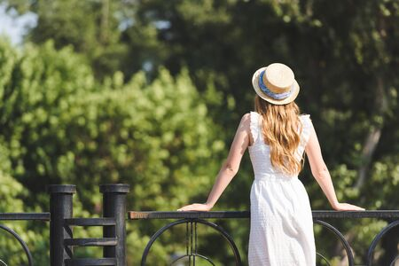 back view of girl in white dress and straw hat leaning on handrail Imagens