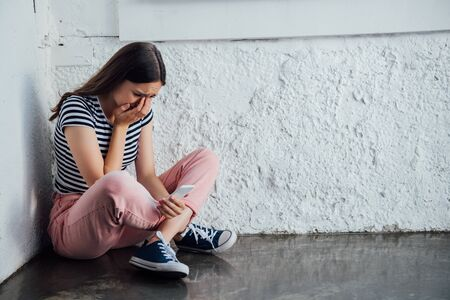 sad crying girl in pink pants sitting near wall and holding smartphone