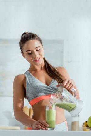 happy girl with sportswear pouring green smoothie in glass from blender Stock Photo
