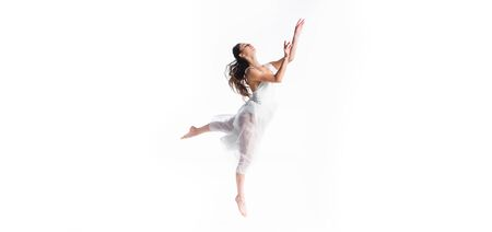 panoramic shot of young attractive ballerina dancing isolated on white