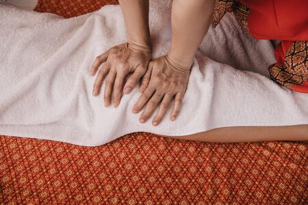 cropped view of masseur doing foot massage to woman in spa salon Stock Photo