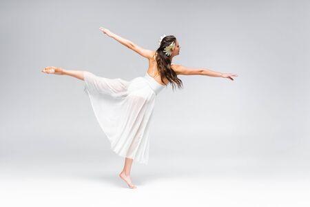 beautiful, elegant ballerina in white dress dancing on grey background
