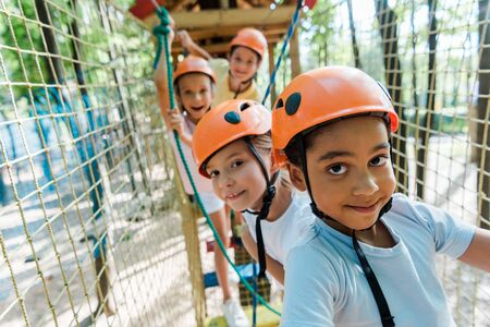 selective focus of cheerful african american boy near happy friends in helmets