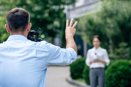 selective focus of cameraman shooting showing gesture and shooting journalist