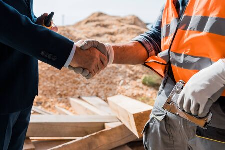 cropped view of constructor and businessman shaking hands