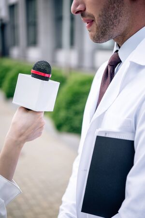 cropped view of journalist holding microphone and talking with doctor 版權商用圖片