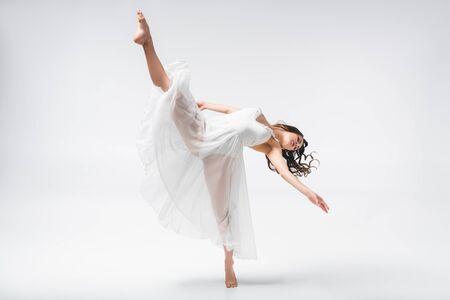Hermosa bailarina en vestido blanco bailando sobre fondo gris