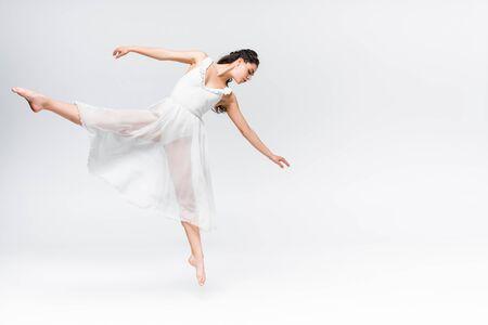 Atractiva joven bailarina bailando en vestido blanco sobre fondo gris