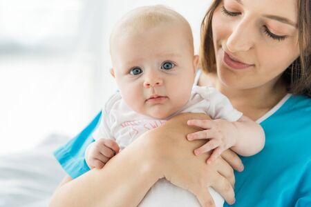 Madre atractiva y joven sosteniendo a su hijo en el hospital