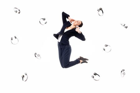 young businesswoman levitating surrounded with flying headphones isolated on white