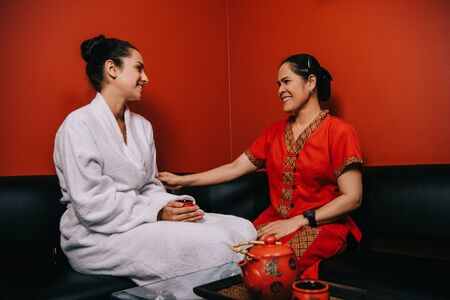 smiling woman in bathrobe and asian masseur talking in spa
