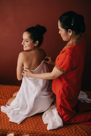 asian woman wrapping with towel attractive woman in spa salon Фото со стока