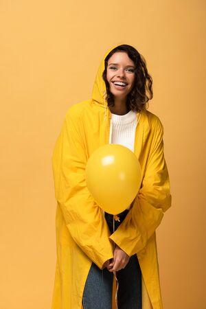 happy curly woman in yellow raincoat holding balloon isolated on yellow Stockfoto