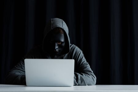 anonymous internet troll in mask typing on laptop keyboard on black Stock Photo