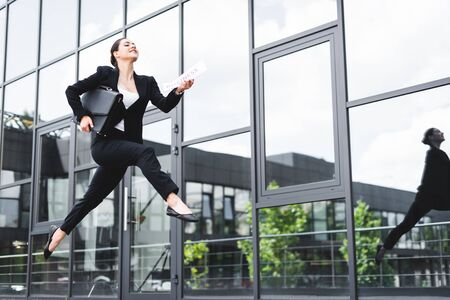 beautiful businesswoman levitating while holding briefcase and newspaper