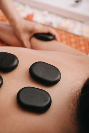 cropped view of masseur doing hot stone massage to woman in spa salon