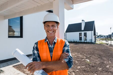 cheerful mature man holding blueprint and smiling near houses