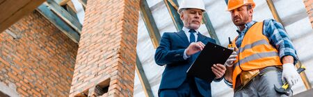 panoramic shot of bearded businessman looking at clipboard near builder