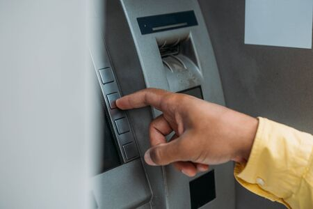cropped view of bi-racial man pressing button on atm machine