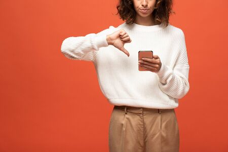 cropped view of woman in autumnal outfit using smartphone and showing thumb down isolated on orange Foto de archivo - 131263197