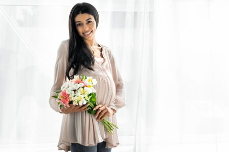 smiling pregnant african american woman holding bouquet in apartment Stok Fotoğraf