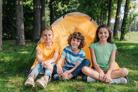 happy curly boy sitting with cute friends near camp