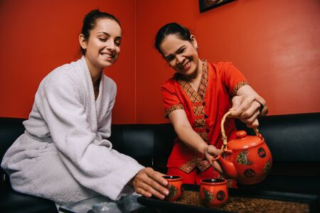 asian masseur pouring tea to cup and attractive woman in bathrobe smiling in spa