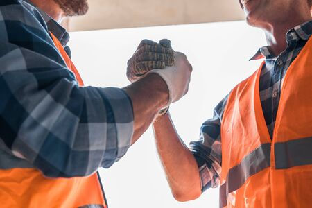 cropped view of constructor shaking hands with coworker Stock Photo