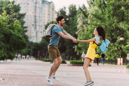 handsome man and asian woman smiling, jumping and holding hands Stock Photo