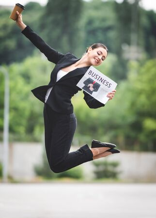 cheerful businesswoman levitating on street while holding coffee to go and business newspaper Stock fotó
