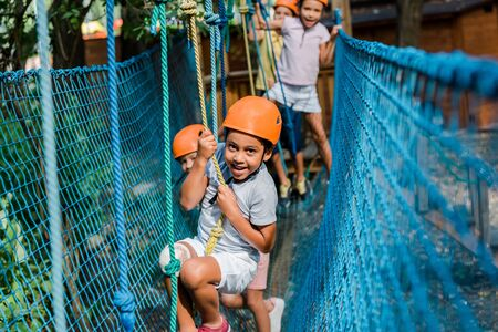 selective focus of smiling african american kid in helmet climbing with friends Stock fotó