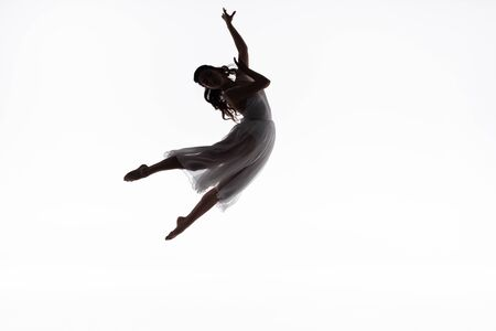 young graceful ballerina jumping while dancing isolated on white