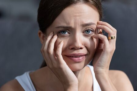 stressed young woman with ring crying and looking at camera Stockfoto
