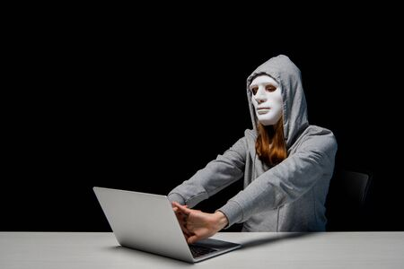 anonymous girl in mask and hoodie sitting near laptop and stretching hands during cyberbullying isolated on black